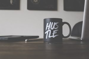 coffee mug with a hustle text on it