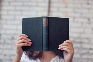 woman hiding behing a old book